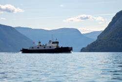 Kayaking on the Lustrafjord. View towards south and the Sognefjord. The ferry is on it´s way to Solvorn.
