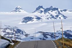 Sognefjellet Mountain Road in May, covered in snow. Smørstabbbreen Glacier with surrounding mountains in the background.